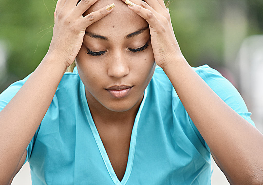 Black women holding her head with stressed look on her face