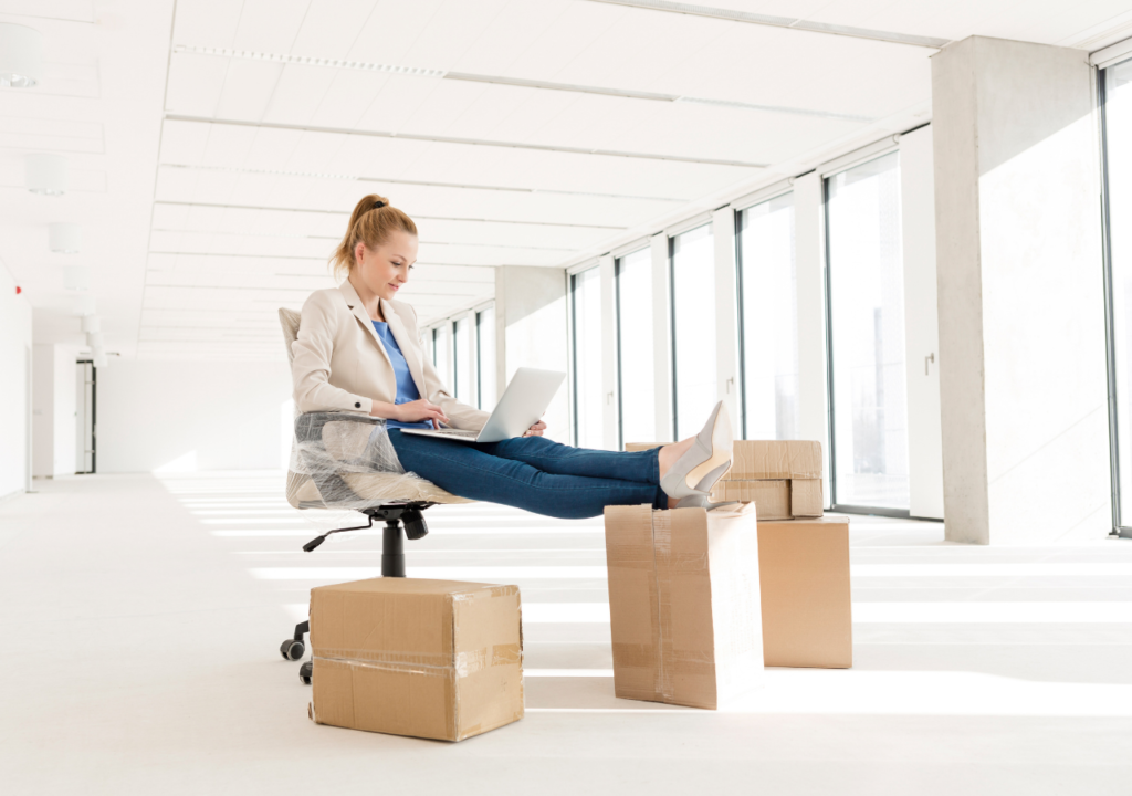 Setting: Office building. Women in a suit jacket and jeans sitting on a chair. She is working on a laptop and is surrounded by boxes.
