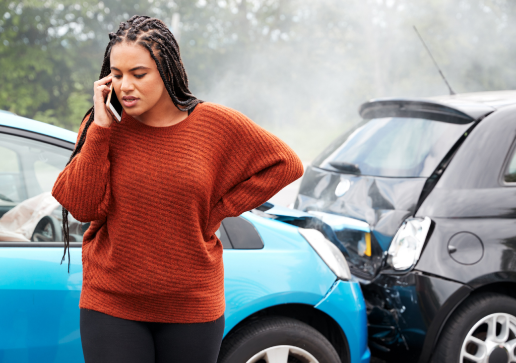 Black woman in an orange sweater on a cell phone. Behind her are two cars that have been in an accident